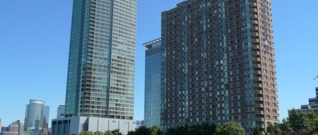 Exterior shot of two condominium buildings overlooking the water.