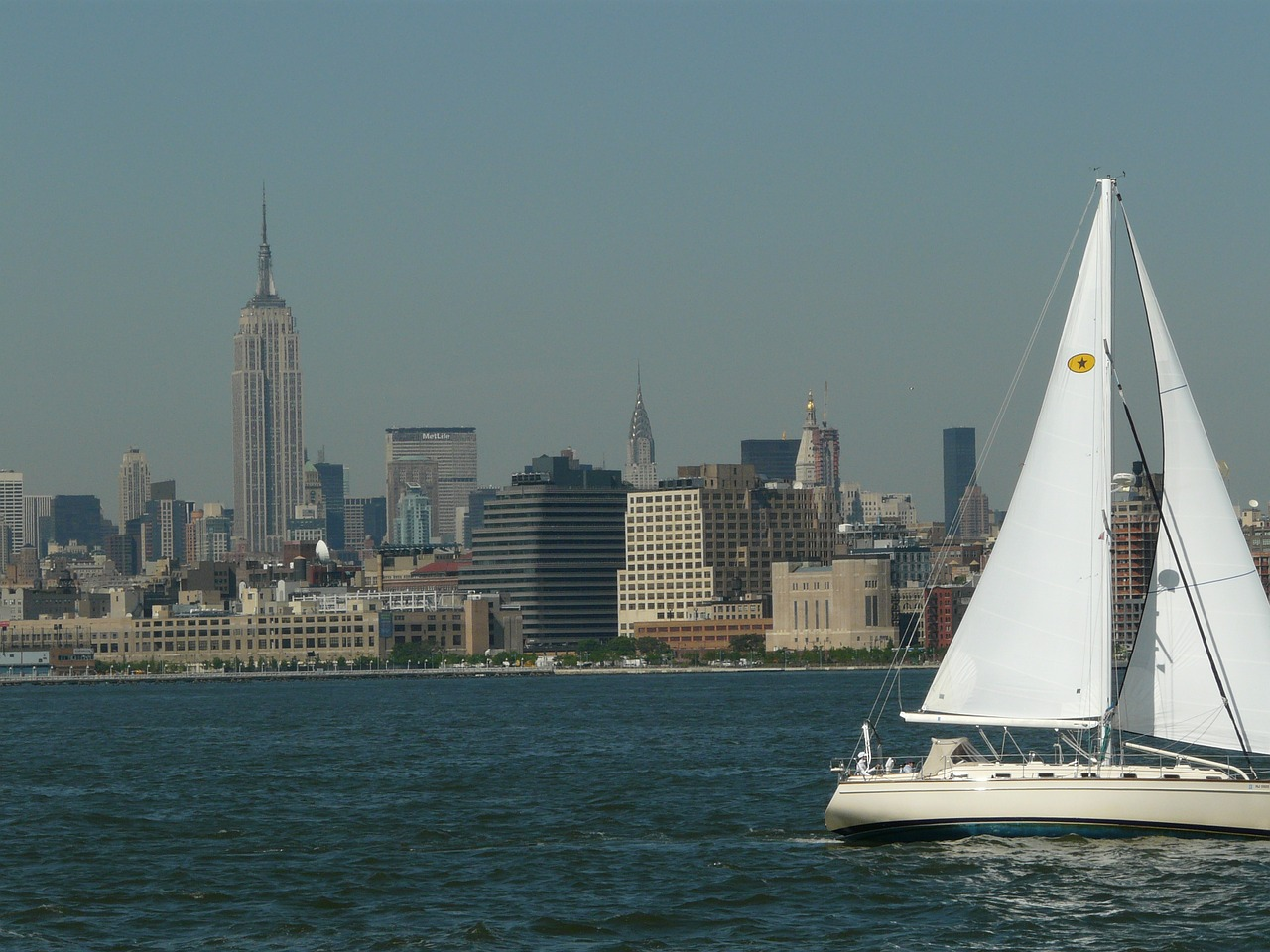Sailboat along Hudson River in front of Manhattan skyline