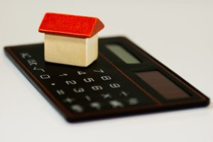 Small red and yellow house sitting on top of a black calculator.