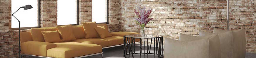 Interior of a loft with exposed brick walls and a yellow couch.